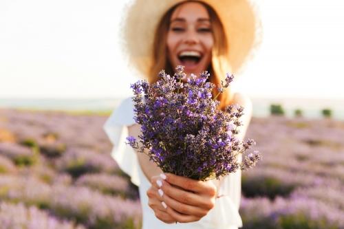 Nettes junges Mädchen im Strohhut, der Lavendelblumenstrauß hält
