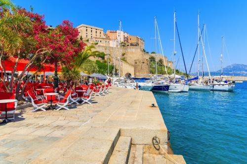Ansicht des Restaurants und der Zitadelle mit Häusern im Hafen von Calvi,Korsika,Frankreich