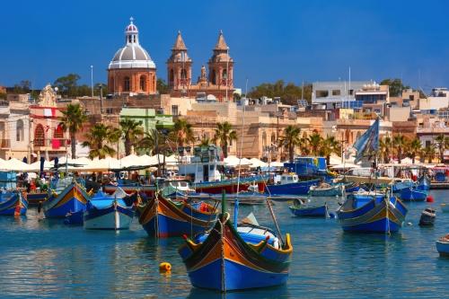 Traditionelle gemusterte bunte Boote Luzzu im Hafen des mediterranen Fischerdorfs Marsaxlokk,Malta