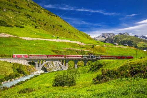 Die Matterhorn - Gotthard - Bahn auf der Viaduktbrücke bei Andermatt in den Schweizer Alpen