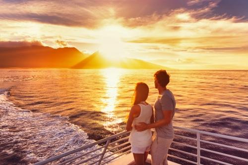 Reisekreuzschiffpaare auf Sonnenuntergangkreuzfahrt in Hawaii-Feiertag. Zwei Touristenliebhaber auf der Flitterwochenreise Sommerferien genießend.