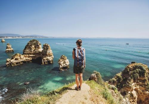Weiblicher Reisender, der das Meer in Lagos-Stadt betrachtet,Algarve-Region,Portugal. Reise- und aktives Lebensstilkonzept