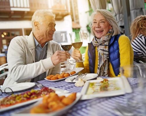 Attraktives älteres Paar, das draußen Tapas isst