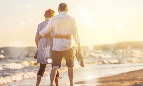 Nahaufnahmeporträt eines älteren Paares, das in Umarmung am Strand spazieren geht
