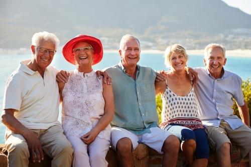 Porträt von den älteren Freunden, die touristischen Markstein auf Gruppenurlaub besuchen