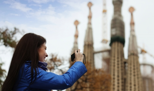 Female tourist   photographing  Sagrada Familia at Barcelona