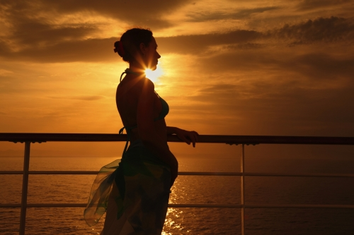 woman standing on deck of cruise ship and looking away.