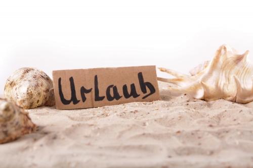 Schild Urlaub, Muscheln und Sand