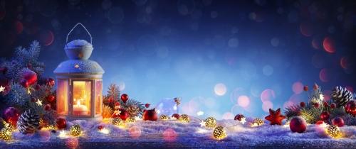 Weihnachtslaterne auf schneebedecktem Tisch mit Tannenzweigen und Verzierungen