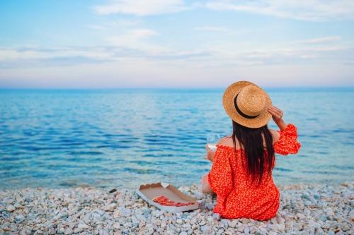 Frau, die ein Picknick mit Pizza am Strand macht