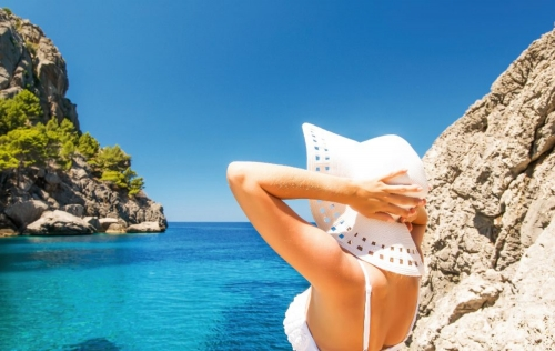 Young woman in white hat looking at sea