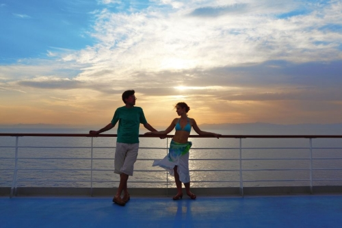 man and woman standing on deck of cruise ship.