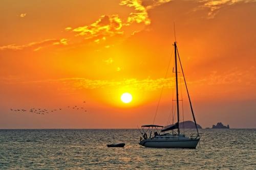 Segelboot im Sonnenuntergang vor der Küste von Ibiza