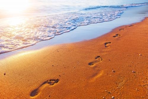 Strand, Wellen und Fußabdrücke bei Sonnenuntergang