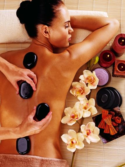 Erwachsene Frau, die Massage mit heißen Steinen im Wellness-Salon
