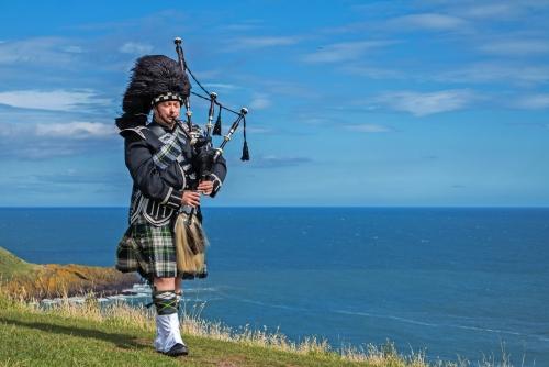 Traditionelle schottische Dudelsackspieler in voller Dresscode mit dem Meer im Hintergrund