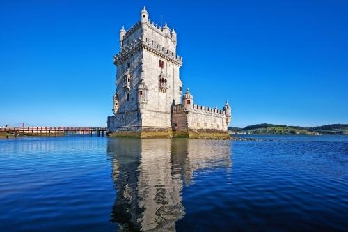 Belem-Turm am Fluss Tejo in Lissabon mit Reflexion in Wasser auf blauem Himmel Hintergrund, Portugal