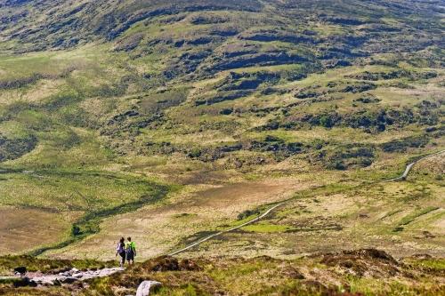 Paare, die hinunter die wilde schroffe Landschaft von Torc-Berg in der Grafschaft Kerry, Irland wandern