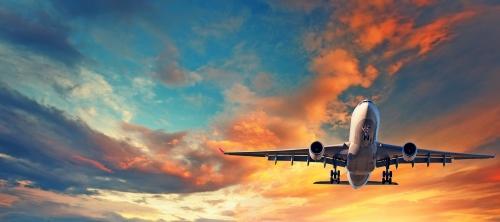 Landung Flugzeug. Landschaft mit weißem Passagierflugzeug fliegt in den blauen Himmel mit mehrfarbigen Wolken bei Sonnenuntergang. Reise-Hintergrund. Passagierflugzeug. Geschäftsreise. Passagierflugzeug