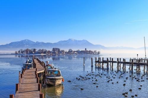 Boote an der Anlegestelle in Gstadt, Bayern, Deutschland, mit See Fraueninsel im Hintergrund an einem kalten Wintertag