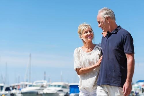 glückliches, älteres paar geht am hafen entlang