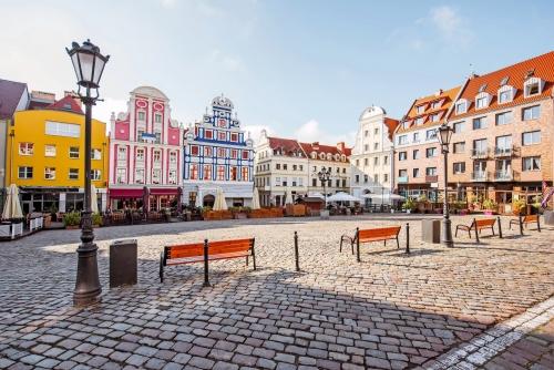 Sehen Sie auf dem Marktplatz mit schönen bunten Gebäuden während des Morgenlichtes in Szczecin-Stadt, Polen an