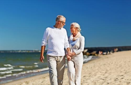 glückliches älteres Paar händchenhalten am Sommerstrand