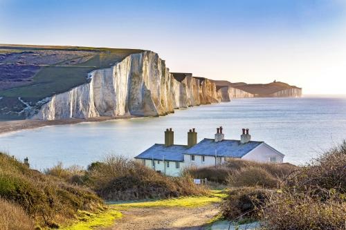 Die Küstenwache-Häuschen und sieben Schwester-Kreide-Klippen gerade außerhalb Eastbourne, Sussex, England, Großbritannien.